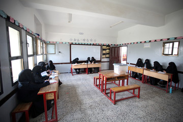 Electoral staff wait for voters during a complementary parliamentary election in Sanaa, Yemen