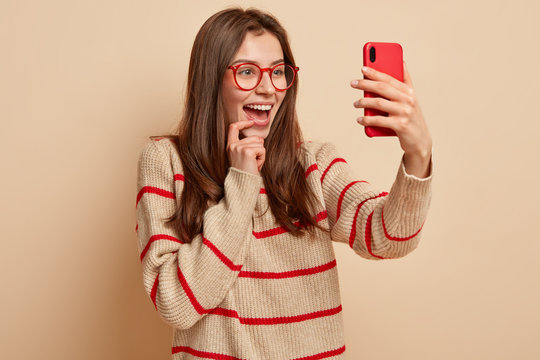 Happy pretty girl makes funny pics, clicks selfie photo on modern cell phone, creats post in social network, enjoys photographing herself, wears transparent glasses, wears casual jumper, isolated
