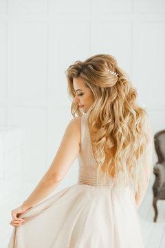 Beautiful blonde woman with greek hairstyle in beige powdery atlas wedding dress posing in studio room.