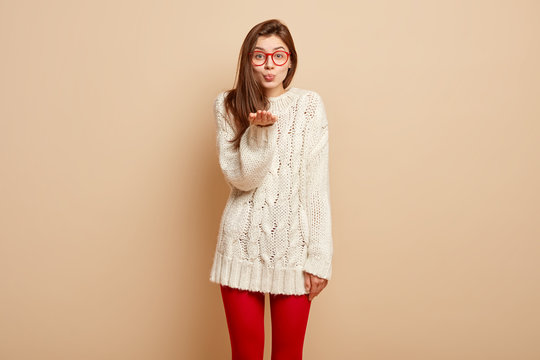 Portrait of attractive woman sends air kiss, keeps palms stretched forward, wears white winter jumper, red leggings, expresses love, has pursed lips, demonstrates gesture of greeting or farewell
