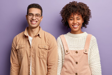 Positive diverse students have broad smiles, express good emootions, stand closely, happy to finish home assigment, wear fashionable clothes, isolated over purple studio wall. Emotions concept