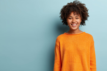 Photo of lovely positive Afro American woman with curly hair, wears orange jumper, being in high spirit stands over blue background with free space for your promotional content. Good emotions concept