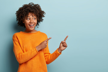 Horizontal shot pleased dark skinned female with Afro haircut, points away with both fore fingers, shows blank space for your promotion, isolated over blue background. People, advertisement concept Wall mural
