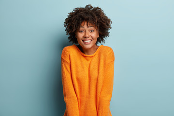 Joyful Afro American girlfriend gets unexpected surprise from boyfriend, has broad smile, feels pleased, wears orange jumper, expresses nice emotions, isolated over blue background. Facial expressions Fototapete