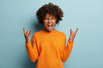 Emotional dark skinned female makes rock n roll gesture, enjoys cool music at party, frowns face, opens mouth, demonstrates hand gesture, dressed in orange jumper, models over blue background Wall mural