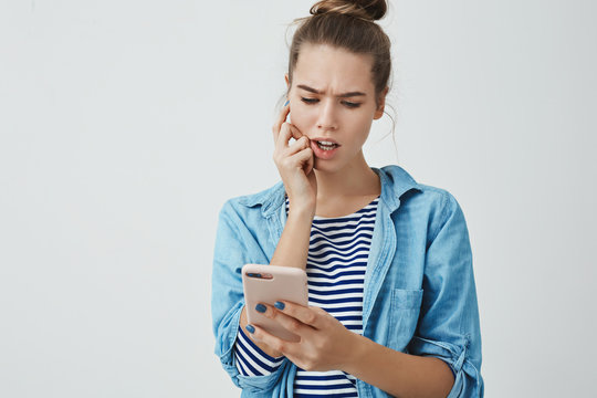 Studio shot perplexed troubled cute young 25s woman checking bills list online, frowning troubled biting finger looking smartphone concerned thoughtful, calculating mind, white studio background
