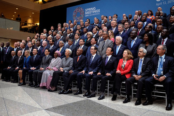 Central bank governors and other global finance officials sit for a group photo at the IMF and World Bank's 2019 Annual Spring Meetings, in Washington