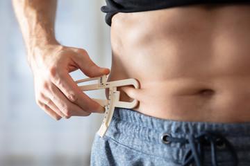 Person Measuring His Body Fat With Caliper