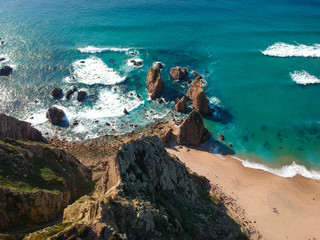Aerial view from a sandy wild beach with rocks. Drone photo