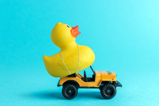 Toy car and yellow rubber duck on blue background. Summer minimal concept.