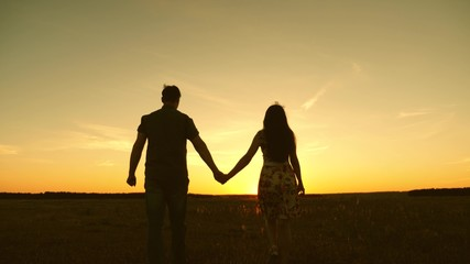 Young couple in love walking across the field holding hands. girl and man go to the sunset. happy family walks in the park in summer in the rays of sun. happy family concept