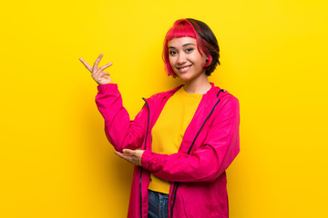 Young woman with pink hair over yellow wall extending hands to the side for inviting to come