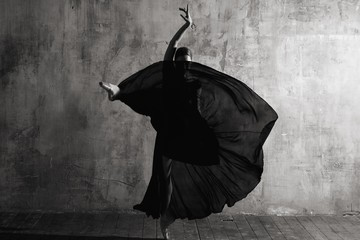 Ballerina in ballroom. Ballet dancer in studio. Black and white monochrome.