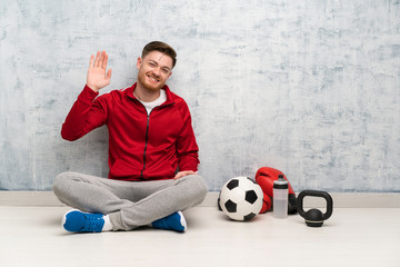 Redhead sport man saluting with hand with happy expression