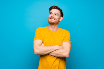 Redhead man over blue wall looking up while smiling Wall mural