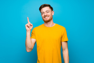 Redhead man over blue wall showing and lifting a finger in sign of the best Wall mural