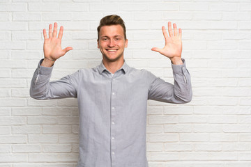 Blonde man over white brick wall counting ten with fingers