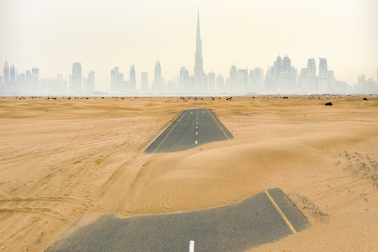 Aerial view of a deserted road covered by sand dunes in the middle of the Dubai desert. Dubai skyline with the Burj Khalifa surrounded by fog in the background. Dubai, United Arab Emirates.