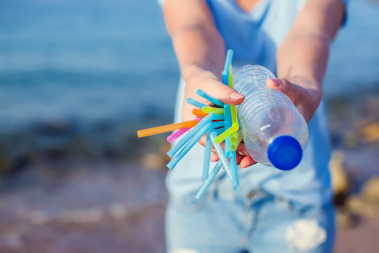 Woman holds plastic bottle and straws in hands on the beach. Beat Plastic Pollution concept.