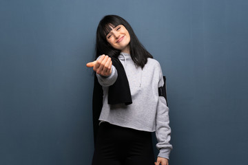 Young sport woman inviting to come with hand. Happy that you came