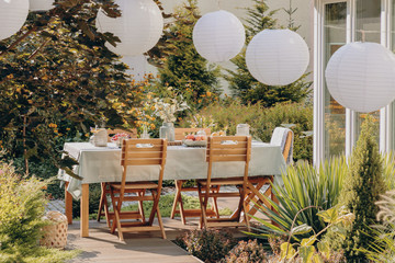 Real photo of round lamps above a table with wooden chairs in a garden