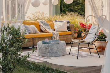 Real photo of an armchair, pouf as a table and wicker couch on a terrace Wall mural