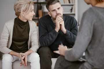 Wife supporting her husband in therapy with the man listening curiously to the counselor