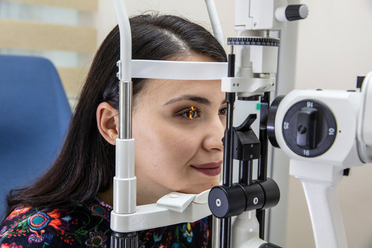 High technology concept health for eyes care - The optician ophthalmology doctor optometrist in the eyes clinic using a binocular slit-lamp to a young woman for an eye control.