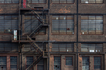 Windows, doors, and fire escape on the exterior of a derelict industrial building, horizontal aspect