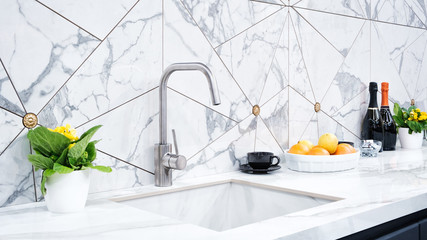 Obraz The interior of the modern kitchen is illuminated with a gray stone countertop with a luxury washbasin and mixer, fruit orange and flowers, a bottle with red wine, champagne and chocolate - fototapety do salonu