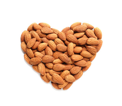 Heart made of almonds on white background, top view. Healthy diet