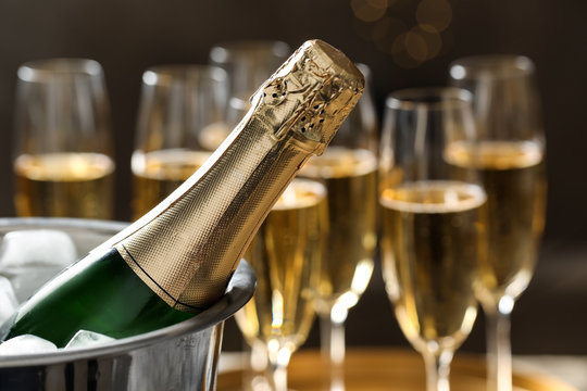 Bottle of champagne in bucket with ice and glasses on blurred background, closeup. Space for text