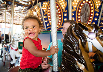 Cute mixed race little boy enjoying a ride on a fun carnival carousel. A happy boy Smiling and having fun riding a carousel ride at the summer carnival