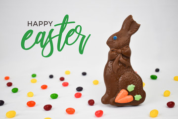 Wall Mural - Chocolate Easter Bunny, Jelly Beans Candy and Happy Easter Calligraphy Text on White Background, Copy Space, Horizontal