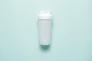 White plastic sports shaker on pastel turquoise background.  Trendy athletics and sport minimal ...
