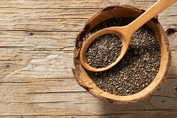 chia seeds in dishes on wooden background, place under the text, view from above