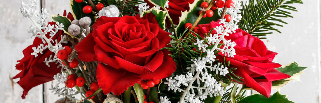 Christmas floral arrangement with roses and other plants, panorama.