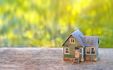 mini toy house, concept of mortgage, construction, rental, using as family and property concept. toy cottage on summer nature background. close up, soft selective focus