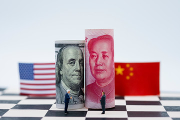 USA dollar and China Yuan banknote with flags on chess table. Its is symbol for tariff trade war crisis or unfair business of 2 biggest economic countries in the world.
