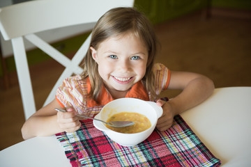 Little girl having lunch and eating soup
