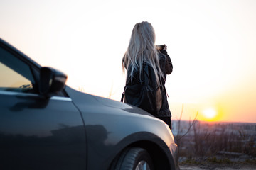 Back view of blonde girl with black backpack, taking photo of sunset.