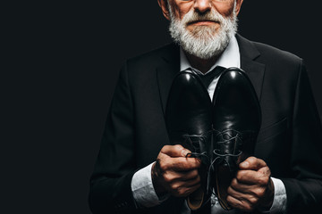 Cropped picture of unrecognizable bearded elderly man in elegant suit showing bespoke leather shoes near his chest over black background. Shoe manufacturing concept