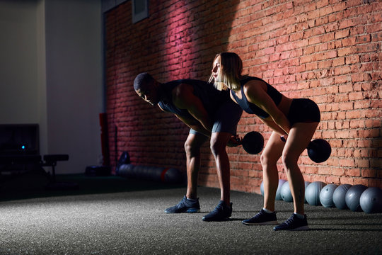 Multi-ethnic couple of diverse athletes are working out at gym with weight. Sporty caucasian woman and african muscular man training with kettlebells in gym against brick wall.