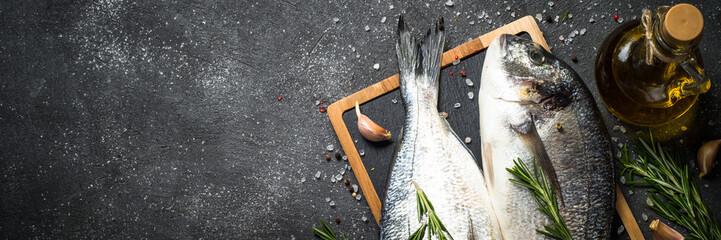 Raw dorado fish on black background. Fototapete