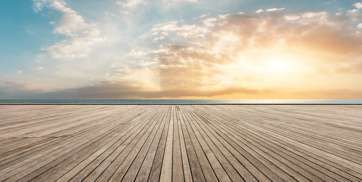 Wooden floor platform and blue sea with sky background
