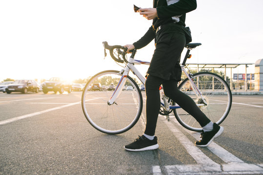 Athlete is a cyclist in sports wear walking around the city with a white bike. Man goes on a bike ride. Cyclist moves around the city on a bicycle.