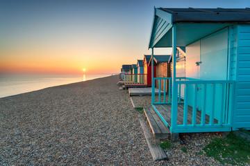 Stunning sunset over seaside beach huts Wall mural