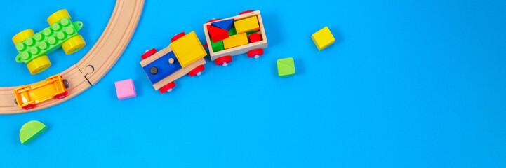 Obraz Baby kid toy background. Wooden toy train with colorful blocks on blue background - fototapety do salonu