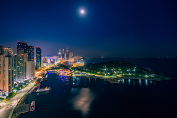 Wall Mural - Busan beach view from roof top of hotel in Busan city in night time with blue sky and full moon