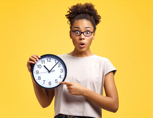 Time to work! Student with shocked face holds clock and points to them. Photo of african american girl wears casual outfit on yellow background. Emotions and pleasant feelings concept.